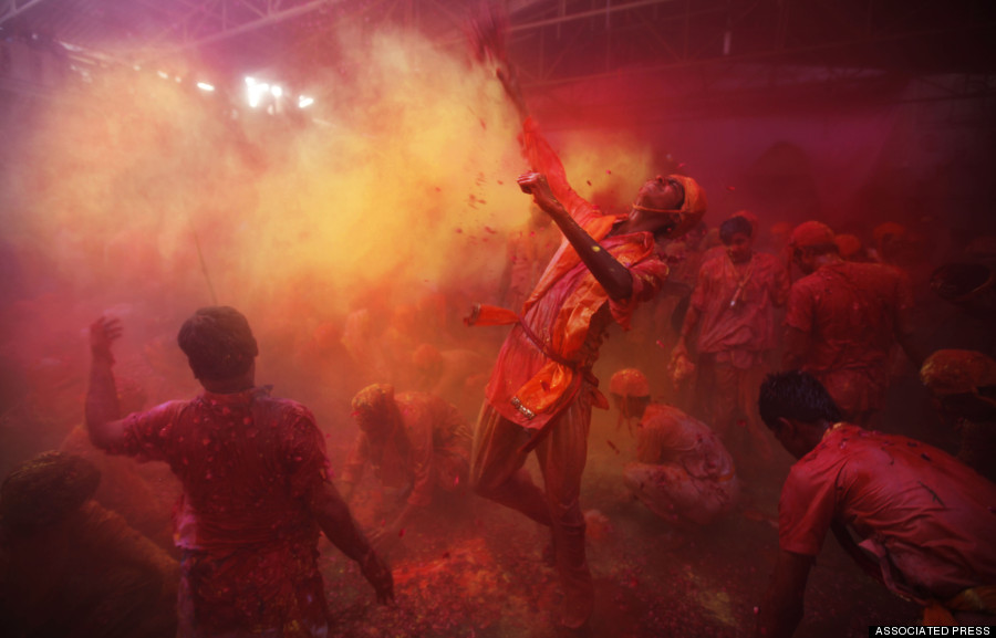 Hindu men from the village of Nangaon throw colored powder on others as they play holi at the Ladali or Radha temple before the procession for the Lathmar Holi festival, the legendary hometown of Radha, consort of Hindu God Krishna, in Barsana 115 kilometers ( 71 miles) from New Delhi, India, Sunday, March 9, 2014. During Lathmar Holi the women of Barsana beat the men from Nandgaon, the hometown of Krishna, with wooden sticks in response to their teasing as they depart the town. (AP Photo/Altaf Qadri)
